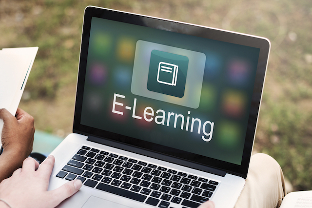 "Close up of a person's hands holding a laptop. The laptop's screen features an icon of a book with the word ""e-learning"" written below."
